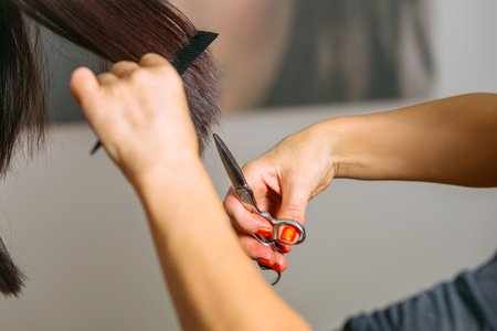 Close up of hairdressers hands shearing long black hair with scissors and comb. Photo. Stock Photo