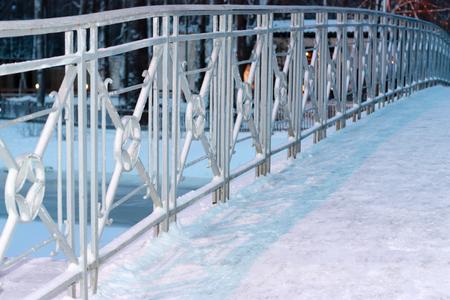 Metal fence of bridge in snow. Horizontally framed shot. Stock Photo