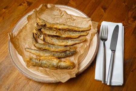 Fried capelin. Wooden background. Horizontally framed shot