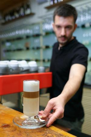 Men barista puts on bar a latte. Serving a client. Focus on beverage. Shallow depth of field. Vertically framed shot.