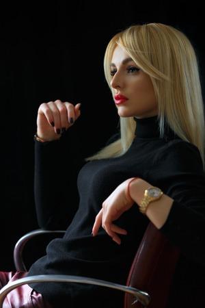 Modèle sexy et beau avec des cheveux blonds directs sur fond noir. Lèvres peintes de rouge à lèvres. Assis sur une chaise. Plan cadré verticalement.