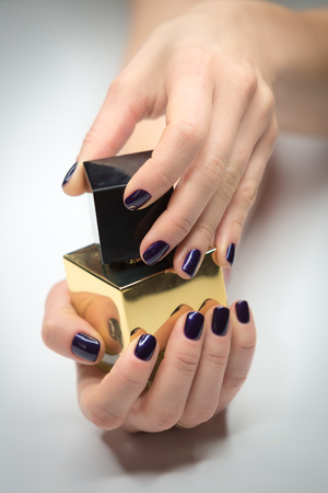 Woman hands with beautiful manicure on white background. In hands a vial of perfume. Vertically framed shot.