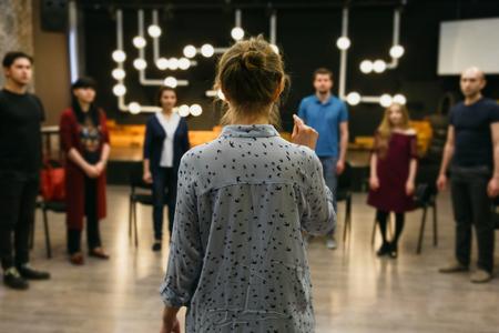 Insegnante di recitazione o coach aziendale si trova di fronte a un gruppo di studenti. Inquadratura orizzontale.