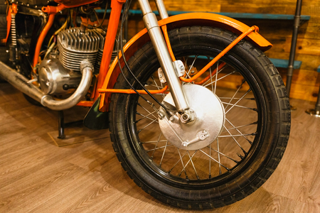 Vintage orange motorcycle detail. Spoke wheel and engine. Horizontally framed shot. Banque d'images