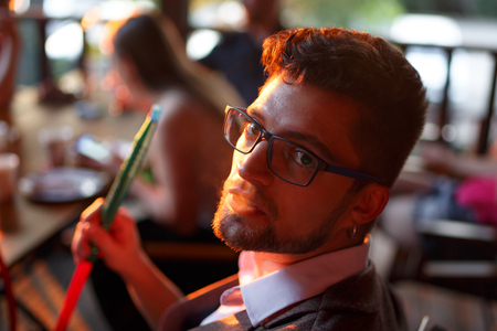 Portrait of a man with glasses. He smokes hookah. Horizontally framed shot. Stock Photo