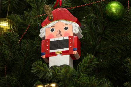 Close-up of nutcracker toy soldier christmas decoration hanging on the Christmas tree. Horizontally framed shot.