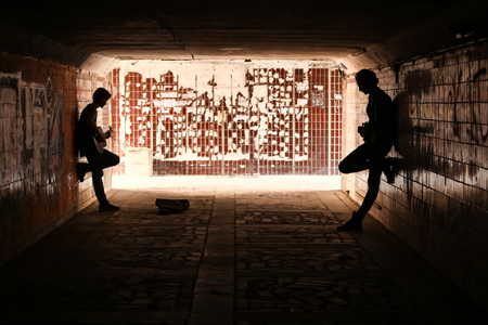 Two street musicians playing guitar in the underpass. Silhouette photo. Vagrant lifestyle. Playing to make money a living. Unemployed musician. Future rock star. Horizontally framed shot.