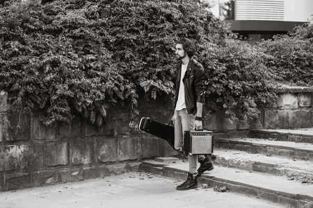 Street musician holding a case with a guitar and amplifier. Vagrant lifestyle. Playing to make money a living. Unemployed musician. Future rock star. Horizontally framed shot. Imagens