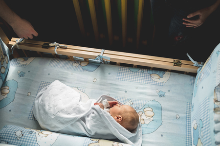 A newborn sleeps in his crib. Next to him are his parents. Man was born. Family life. Horizontally framed shot. Standard-Bild