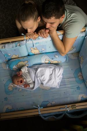 Woman and man look at newborn. Boy cries in his crib. Standard-Bild