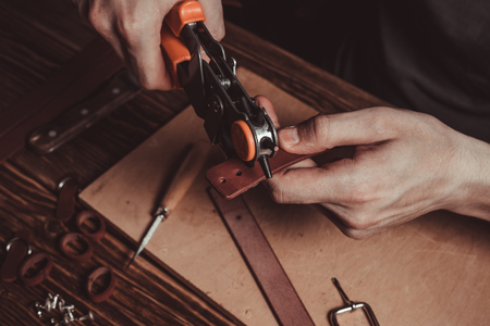 Master holding a hole punch and a piece of leather. On brown wooden table scattered with tools and accessories. Photo. Reklamní fotografie