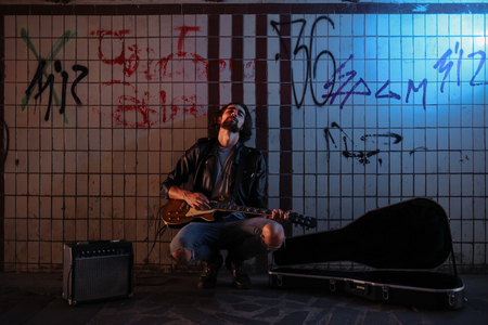 A street musician playing on guitar in the underpass. Stock Photo