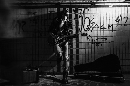 A street musician playing on guitar in the underpass.