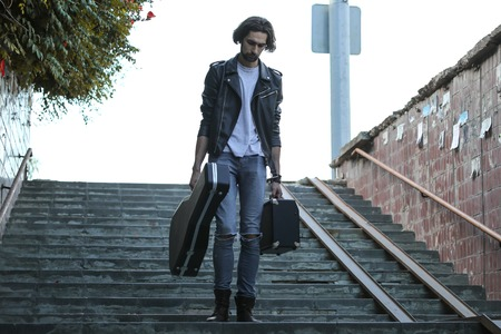 Street musician holding a case with a guitar and amplifier. Goes down the stairs to the underground passage. Stock Photo