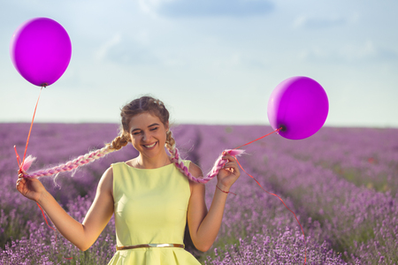 Portrait of a happy and joyful girl in yellow dress with a balloons in her hands. In the background, a lavender field and blue sky. Horizontally framed shot. Banque d'images