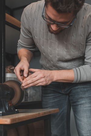 Leather craftsman sharpens knife for cutting leather on sander. Handmade concept. Concept of small business to create leather products. Vertically framed shot.