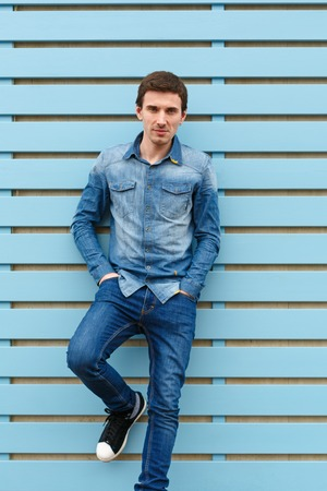 Growth portrait of brunet cute young man in casual stylish denim wear. Put his hands in his pockets. He leaned against blue wooden wall. Vertically framed shot.