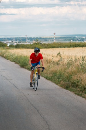 A cyclist in red blue form rides on a road bicycle along field. Vertically framed shot.