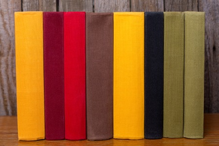 A pile of old colorful books on table. On a wooden background. Banque d'images - 125038220