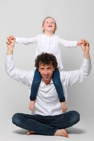 A little sweet girl sitting on shoulders of his father. The man sits crossed legs. They laugh merrily. The concept of happy parenting and happy childhood. On white background. Vertically framed shot. Фото со стока