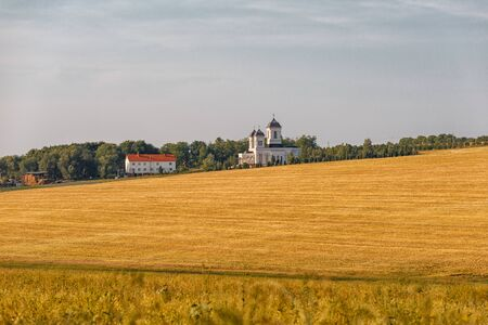 Orthodox Church among the fields of wheat. White Church and outbuildings. Agricultural fields. Horizontally framed shot.