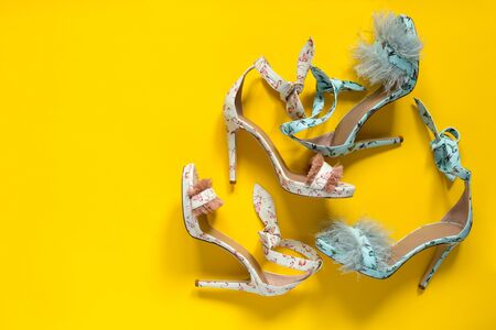 Summer womens high-heeled shoes. Flamingo hummingbirds and feathers. Yellow paper background. Horizontally framed shot.