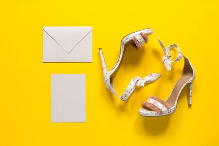 Summer women's high-heeled shoes. Pink flamingos and feathers. Envelope and postcard. Yellow paper background. Horizontally framed shot. Archivio Fotografico - 129646505
