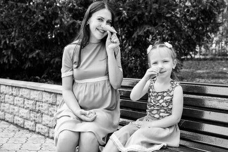 Mom and daughter sit on bench and play with waffle cups. They make a nose like Pinocchio's. Horizontally framed shot.