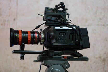 Process of filming. Big movie camera on a tripod. Horizontally framed shot.