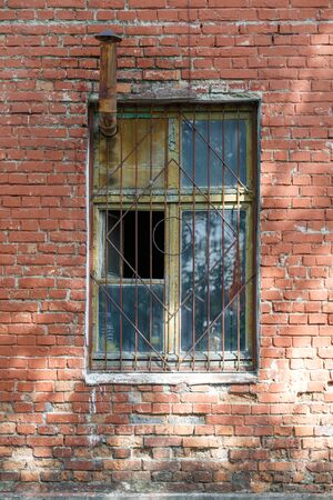 Old brick wall with window. Window has a grate and a chimney. Vertically framed shot.