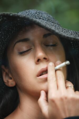 Close up portrait of a beautiful brunette in black hat. She has closed her eyes and is smoking a cigarette. Vertically framed shot.