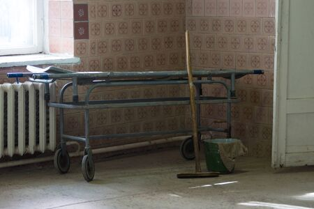Old stretcher gurney bed in the hospital hallway. Wooden mop bucket and rag. A horrible old hospital or morgue. Horizontally framed shot.
