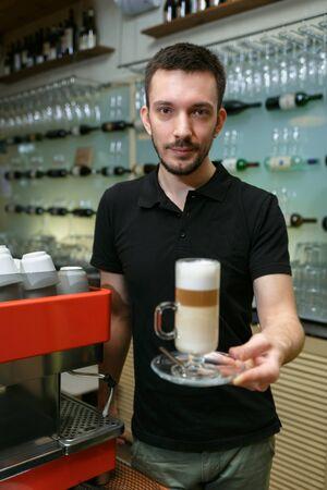 Men barista hold glass of latte. Serving a client. Vertically framed shot. 写真素材