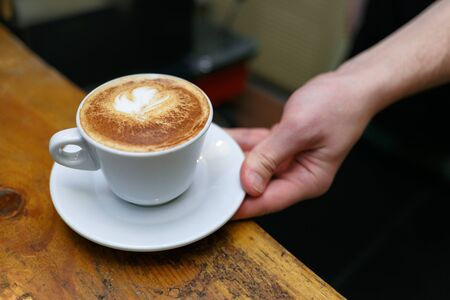 Hand barista holding and serving cup of coffee. Horizontally framed shot.