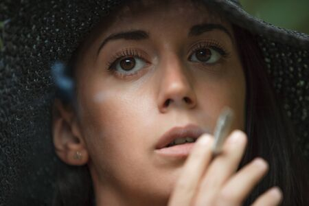 Close up portrait of a beautiful brunette in black hat. She smokes a cigarette. Horizontally framed shot.
