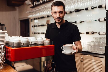 Men barista hold cup of coffee. Serving a client. Focus on beverage. Shallow depth of field. Horizontally framed shot.