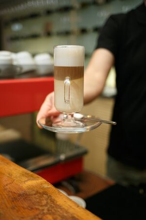 Hand barista holding and serving glass of latte. Horizontally framed shot.