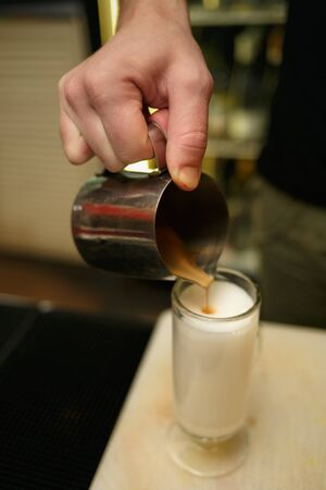Professional barista pouring milk to make cup of coffee. Shallow depth of field. Horizontally framed shot.