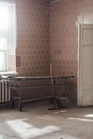 Old stretcher gurney bed in the hospital hallway. Wooden mop bucket and rag. A horrible old hospital or morgue. Vertically framed shot.