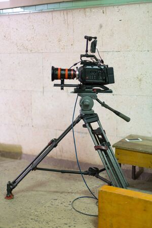 Process of filming. Big movie camera on a tripod. Vertically framed shot.