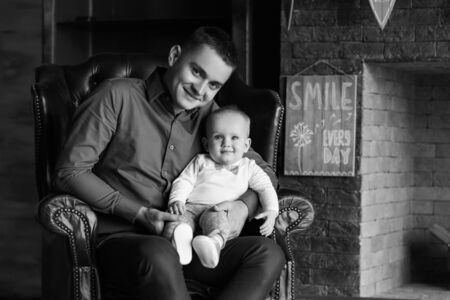 A father sits in a chair and holds his little son in his lap. They are both smiling. Family life. Horizontally framed shot. Reklamní fotografie