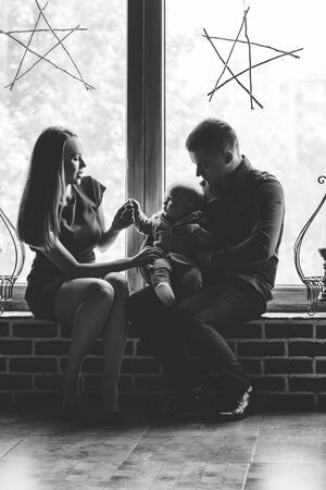 Parents and their child sitting at the window. Mom, dad and baby. Portrait of young family. Happy family life. Man was born. Vertically framed shot. Фото со стока