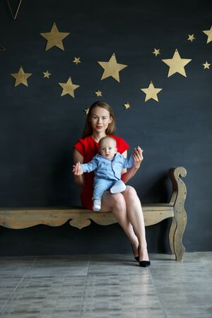 Mother and child sitting on a bench. Portrait of young family. Happy family life. On gray wall gold stars. Vertically framed shot.