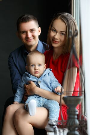 Parents and their child sitting at the window. Mom, dad and baby. Portrait of young family. Happy family life. Man was born. Vertically framed shot.