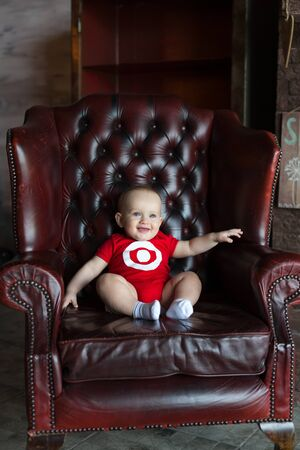 A little boy sits in a leather chair. Happy family life. Man was born. Vertically framed shot.