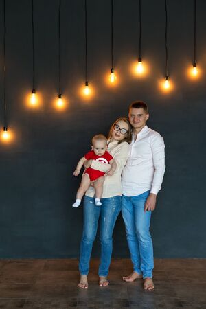 Mom, dad and baby. Portrait of young family. Happy family life. Man was born. Lights are on in background. Vertically framed shot.