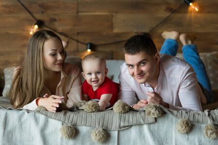 Parents and their child lying on bed. Mom, dad and baby. Portrait of young family. Happy family life. Man was born. Horizontally framed shot. Reklamní fotografie