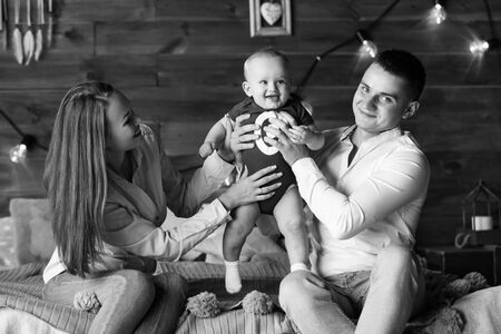 Parents and their child sitting on bed. Mom, dad and baby. Portrait of young family. Happy family life. Man was born. Horizontally framed shot. Reklamní fotografie