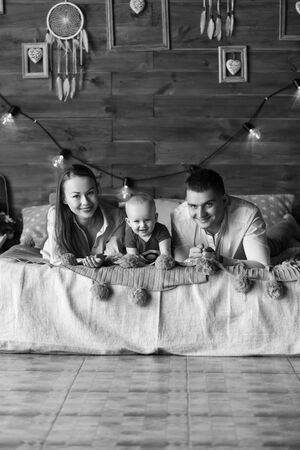 Parents and their child lying on bed. Mom, dad and baby. Portrait of young family. Happy family life. Man was born. Vertically framed shot.