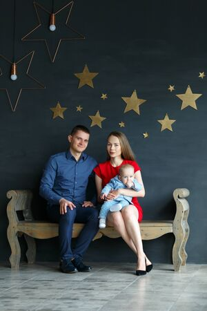 Parents and their child sitting on a bench. Mom, dad and baby. Portrait of young family. Happy family life. Man was born. On gray wall gold stars. Vertically framed shot. Reklamní fotografie